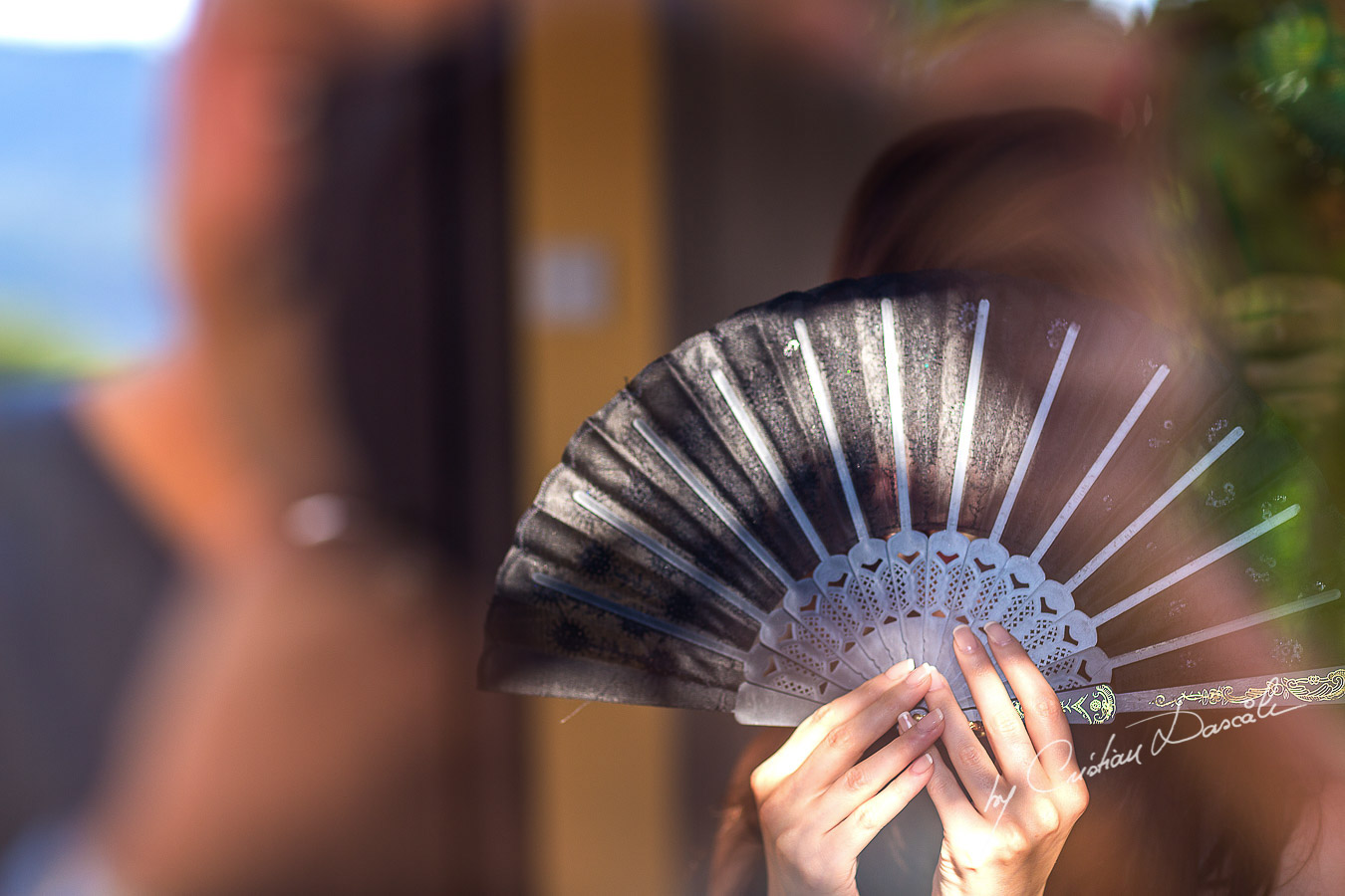 Rindala, the bride hiding from the photographer using a traditional fan.