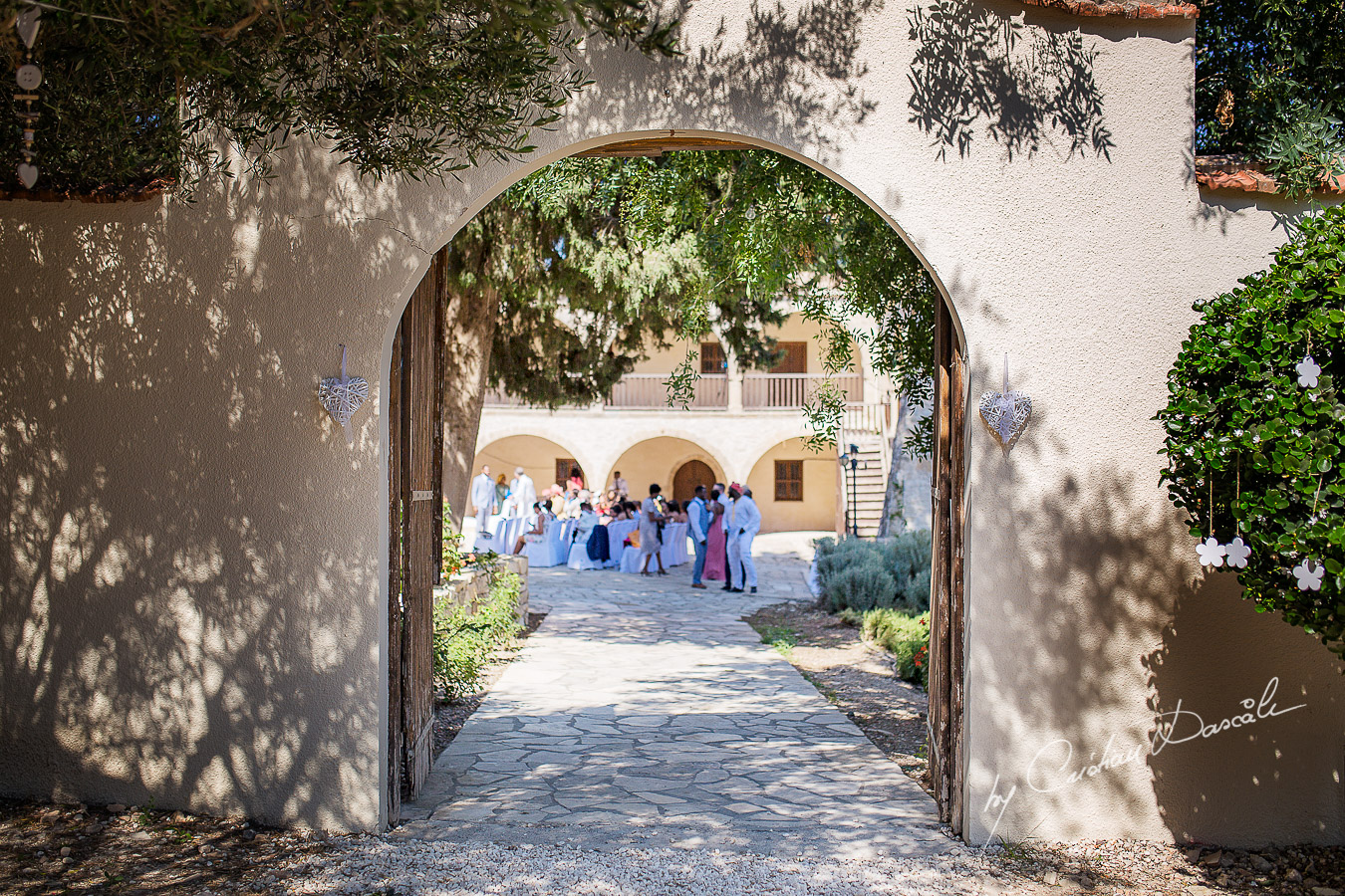 Wedding guests photographed through the Minthis Hills monastery gate, moments captured at a wedding at Minthis Hills in Cyprus, by Cristian Dascalu.