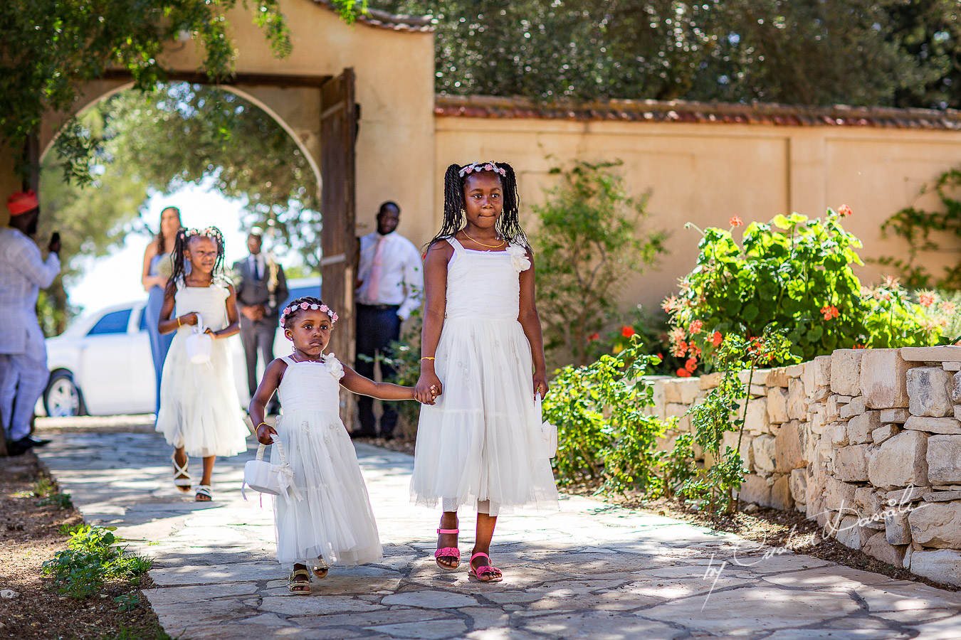 Moments with flower girls announcing the arrival of the bride captured a wedding at Minthis Hills in Cyprus, by Cristian Dascalu.