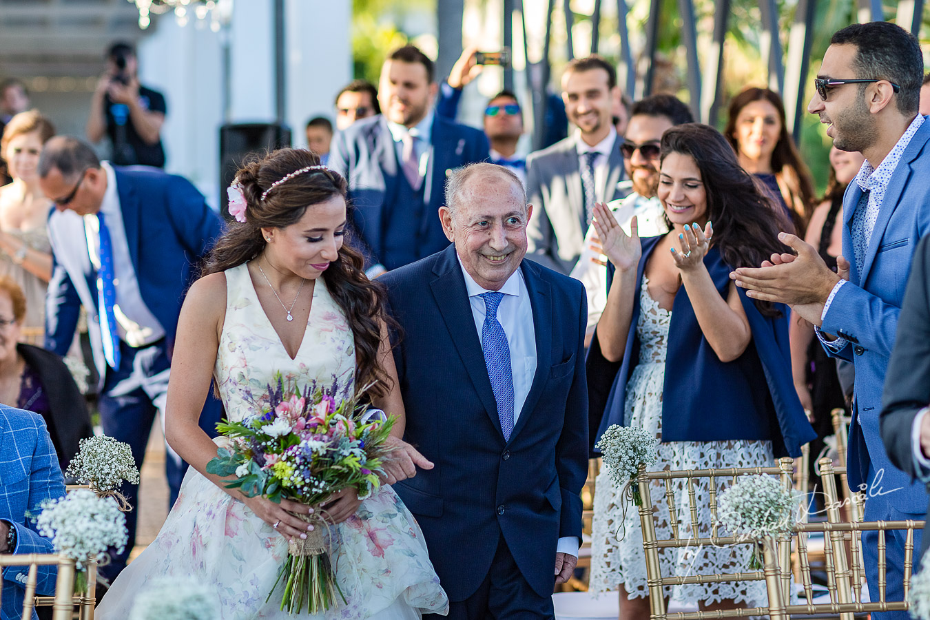 The bride coming down the isle with her father photographed during the ceremony, as part of an Exclusive Wedding photography at Grand Resort Limassol, captured by Cyprus Wedding Photographer Cristian Dascalu.