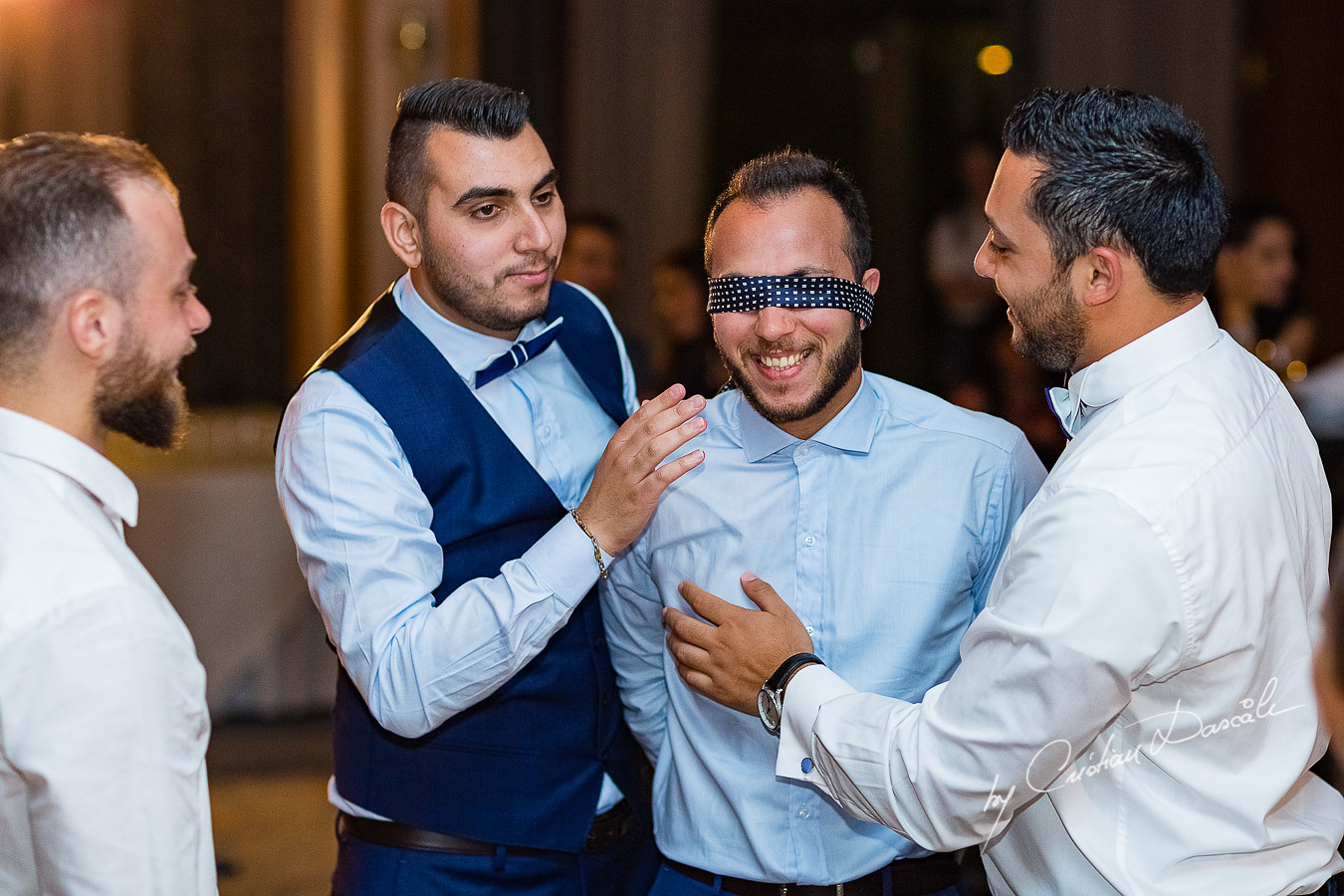 Moment when the groom is prepared for the garter photographed as part of an Exclusive Wedding photography at Grand Resort Limassol, captured by Cyprus Wedding Photographer Cristian Dascalu.