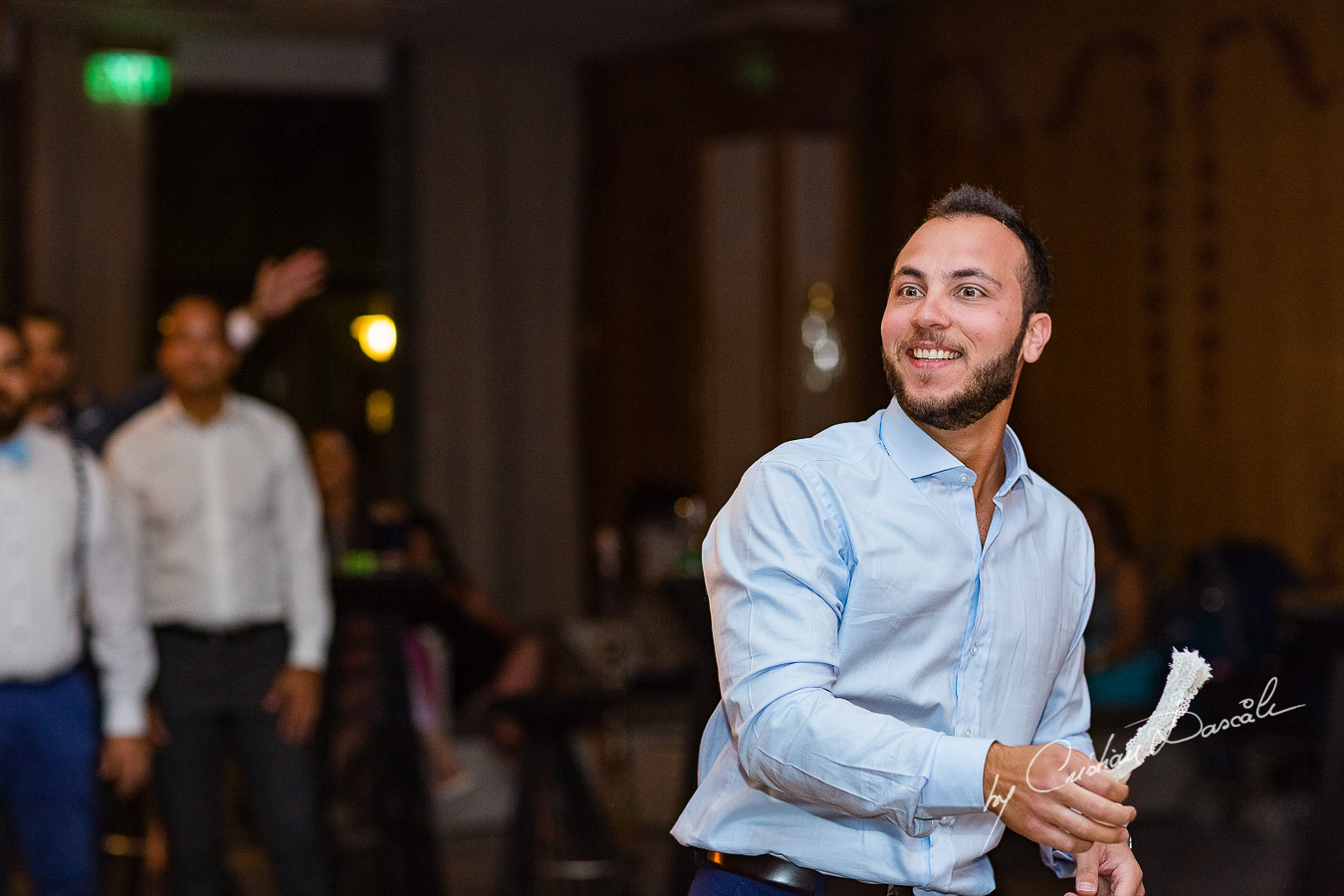 Moment when the groom is throwing the garter photographed as part of an Exclusive Wedding photography at Grand Resort Limassol, captured by Cyprus Wedding Photographer Cristian Dascalu.