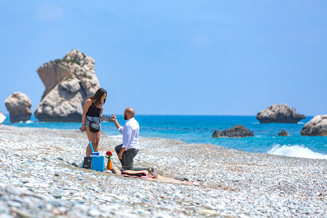 Christian kneels in front of Jana, asking her to marry him, at the secret location of the Aphrodite Rocks in Paphos, Cyprus.