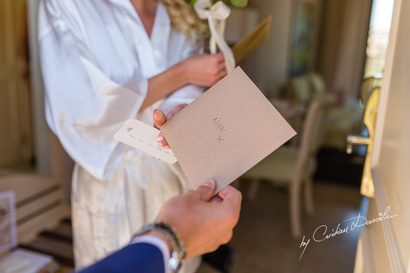 The Bride gives back to the Bestman an envelope for the Groom captured at Aphrodite Hills Resort before the wedding ceremony by Cristian Dascalu.