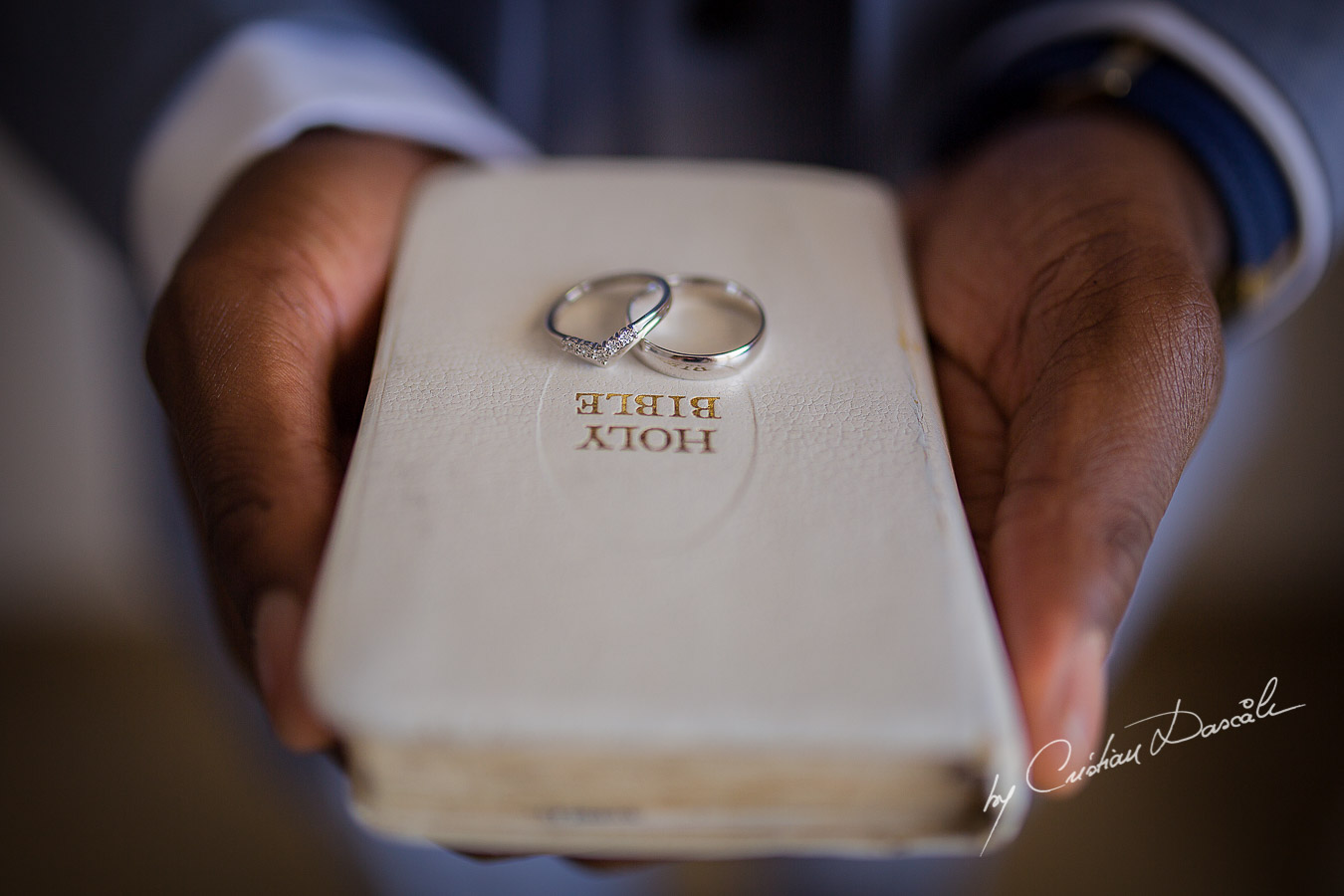 The wedding rings captured on the Holy Bible at a wedding at Minthis Hills in Cyprus, by Cristian Dascalu.