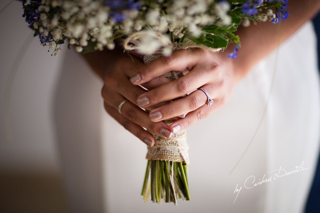 Real moment captured with the bridal bouquet and the engagement ring at a wedding at Minthis Hills in Cyprus, by Cristian Dascalu.