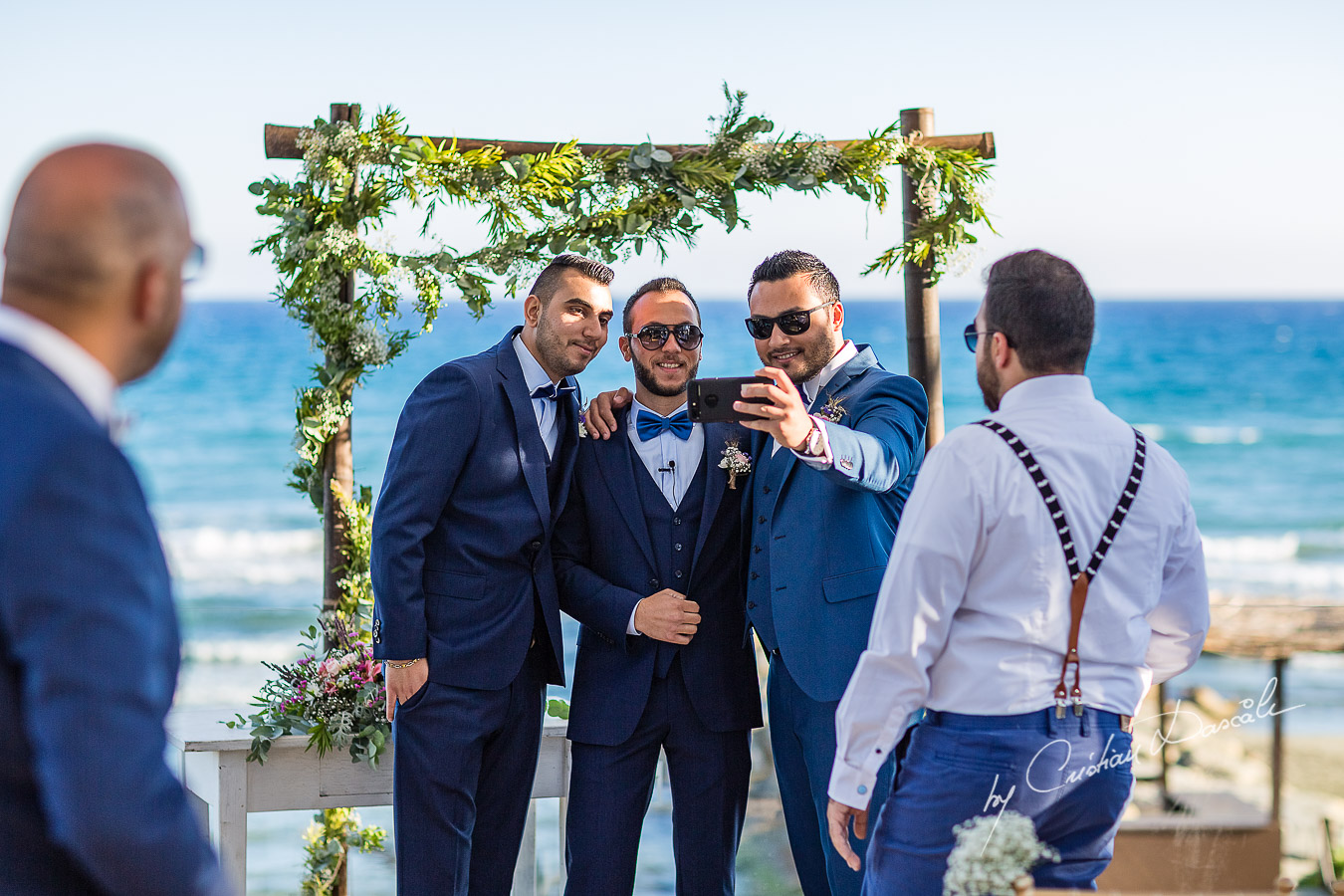 Groom and best men posing for selfies before the reception, as part of an Exclusive Wedding photography at Grand Resort Limassol, captured by Cyprus Wedding Photographer Cristian Dascalu.