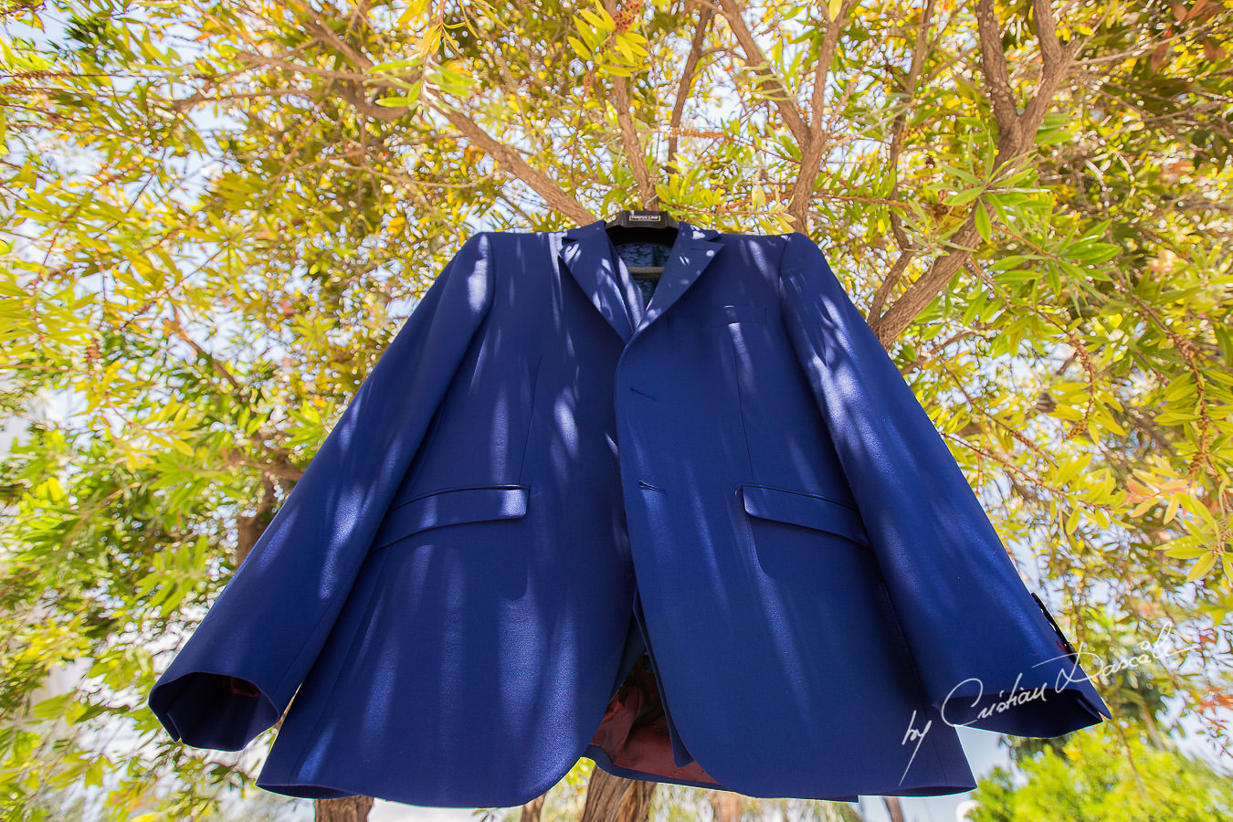 Groom's suit hanged on a tree in front of the groom's house, captured at a wedding in Cyprus by Photographer Cristian Dascalu.