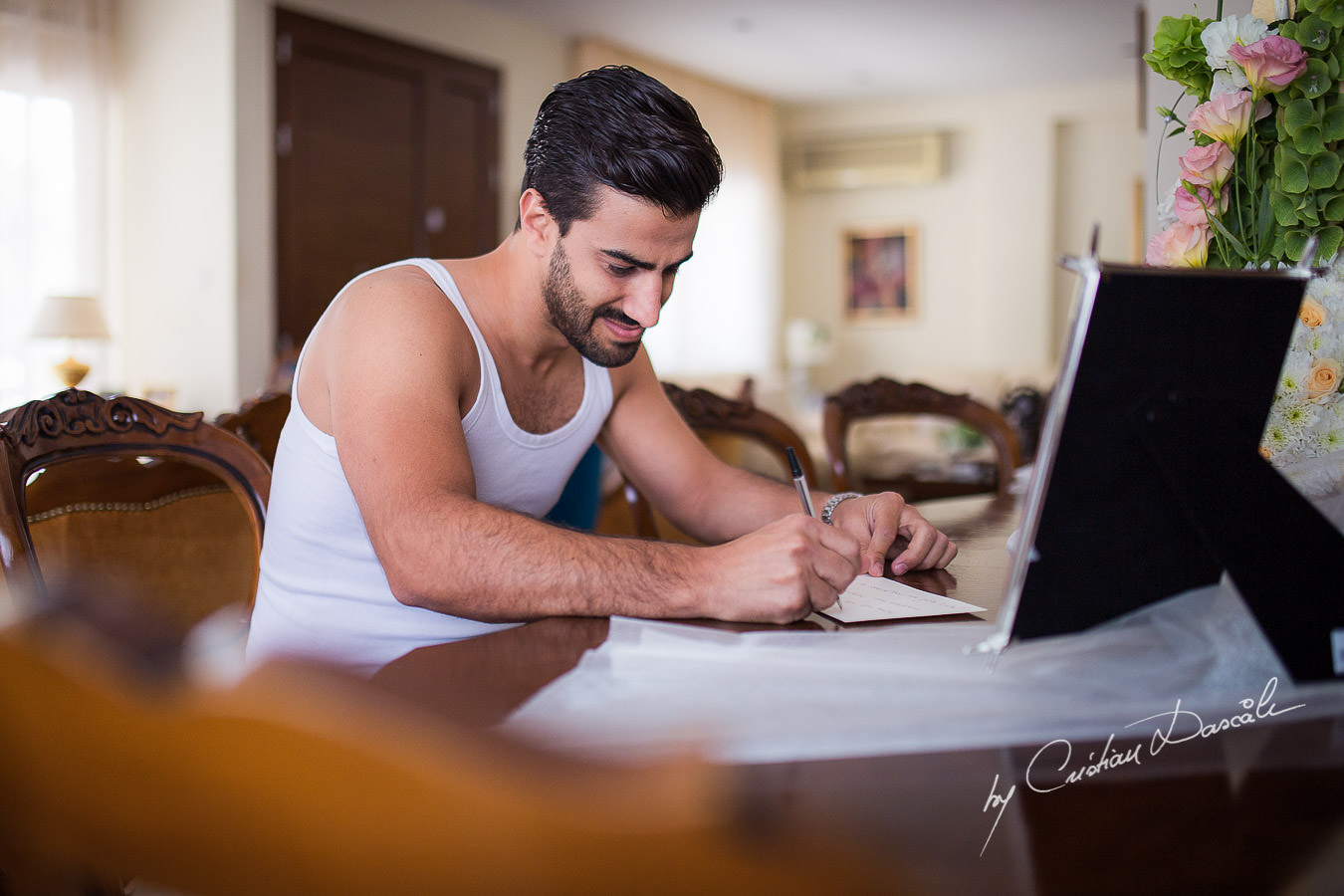 The Groom, Alexis, writing a letter to his bride, captured at a wedding in Cyprus by Photographer Cristian Dascalu.
