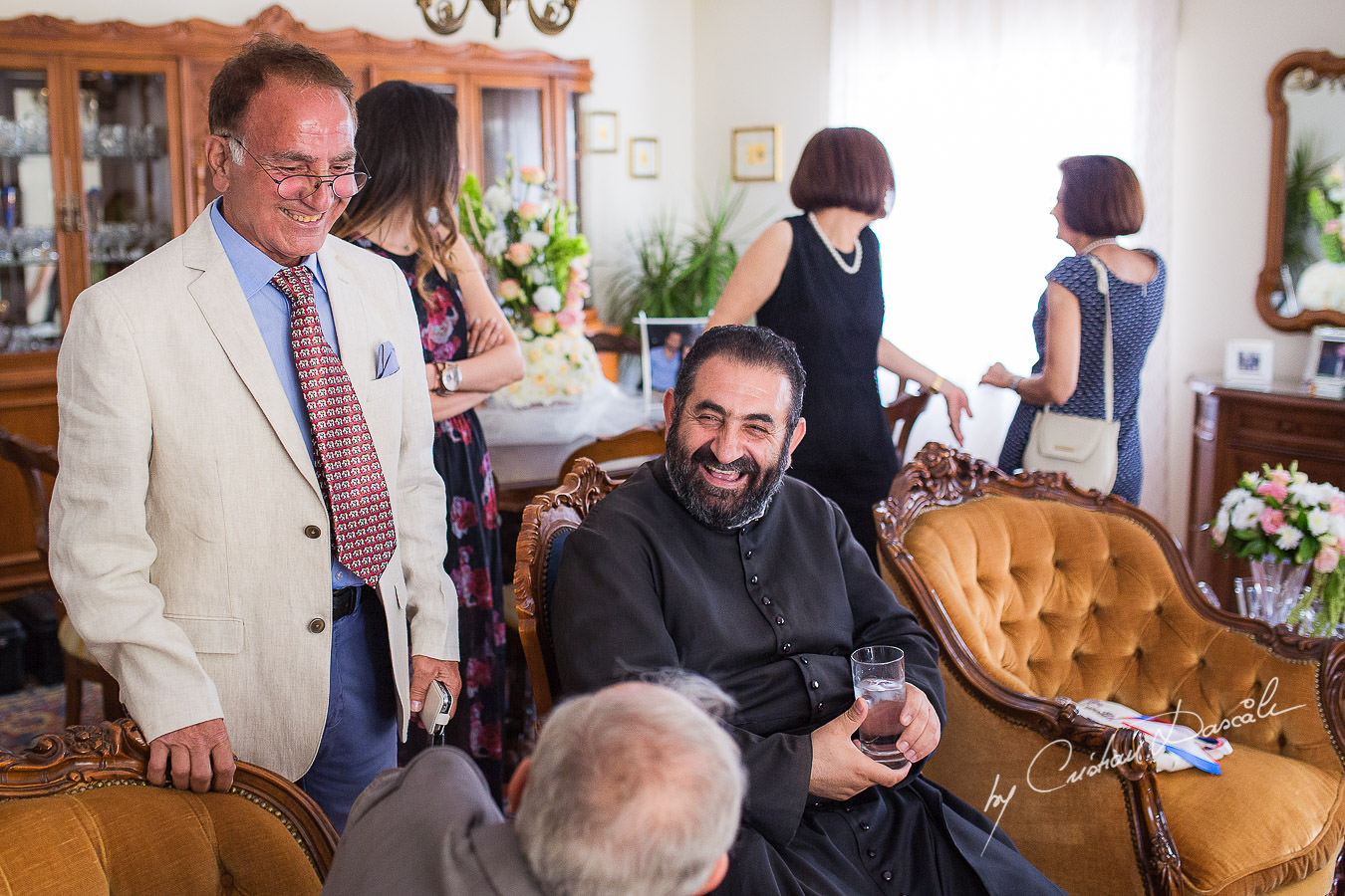 The priest, laughing and joking with wedding guests at the groom's house, captured at a wedding in Cyprus by Photographer Cristian Dascalu.