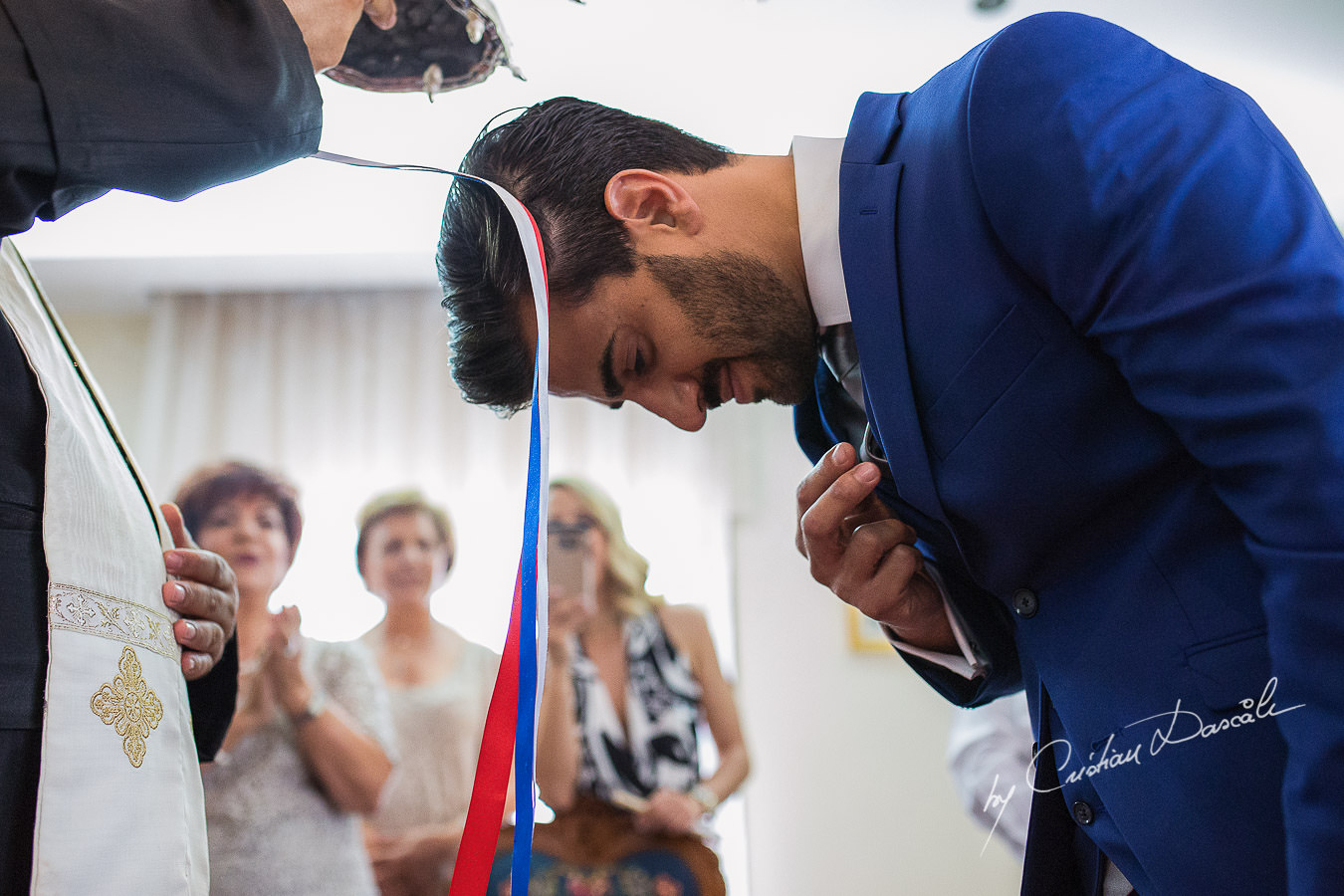 The groom making the sign of the Holy Cross during a traditional ceremony, captured at a wedding in Cyprus by Photographer Cristian Dascalu.