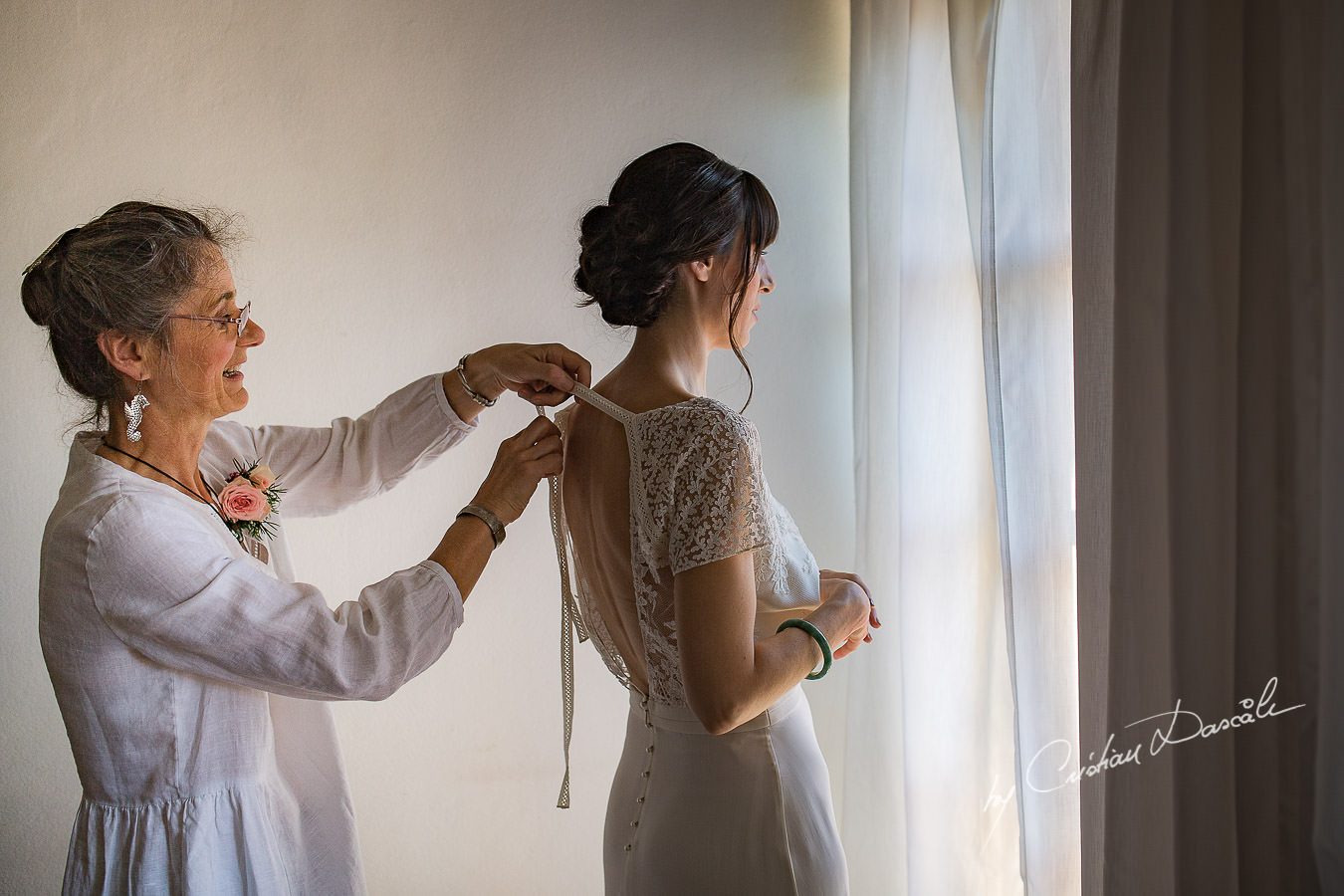 A beautiful wedding day at the Vasilias Nikoklis Inn in Paphos, captured by Cristian Dascalu. Sarah's mother is getting her ready for the wedding ceremony.
