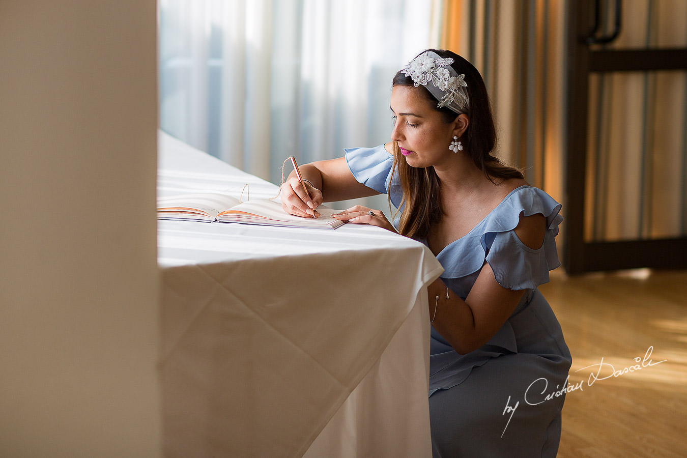 Guests writing wishes int he guest book, moments photographed by Cristian Dascalu at Athena Beach Hotel in Paphos, Cyprus, during a symbolic wedding.