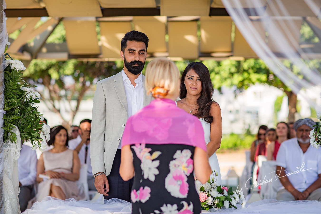 Bride and groom in front of the celebrant, moments photographed by Cristian Dascalu at Athena Beach Hotel in Paphos, Cyprus, during a symbolic wedding.