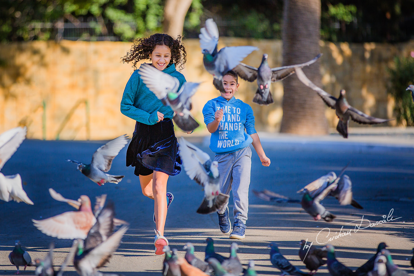 Young brother and sister running through the pigeons, moments captured by Cristian Dascalu during a beautiful Limassol family photography photo session.