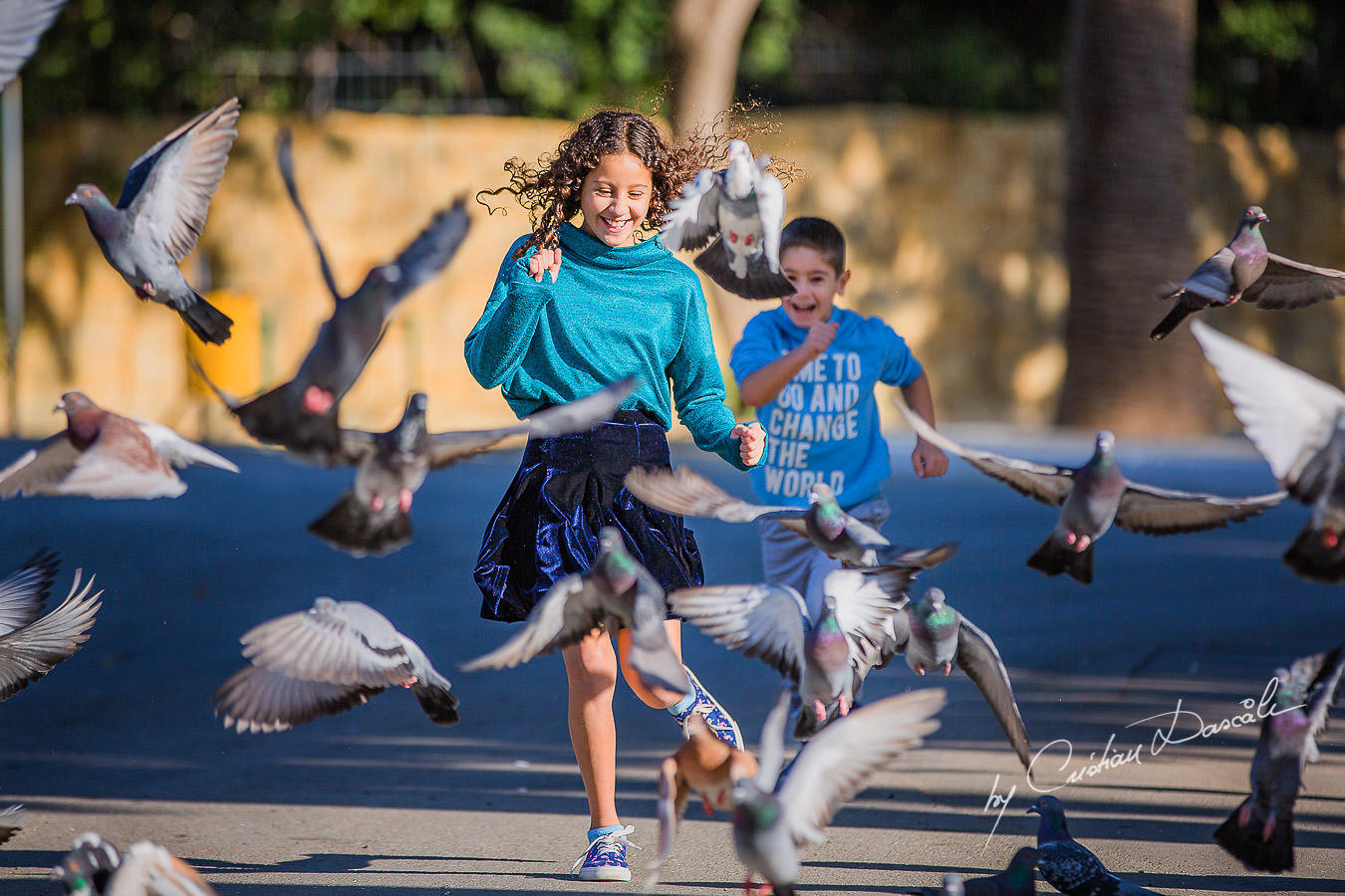 Young brother and sister running through birds, , moments captured by Cristian Dascalu during a beautiful Limassol family photography photo session.