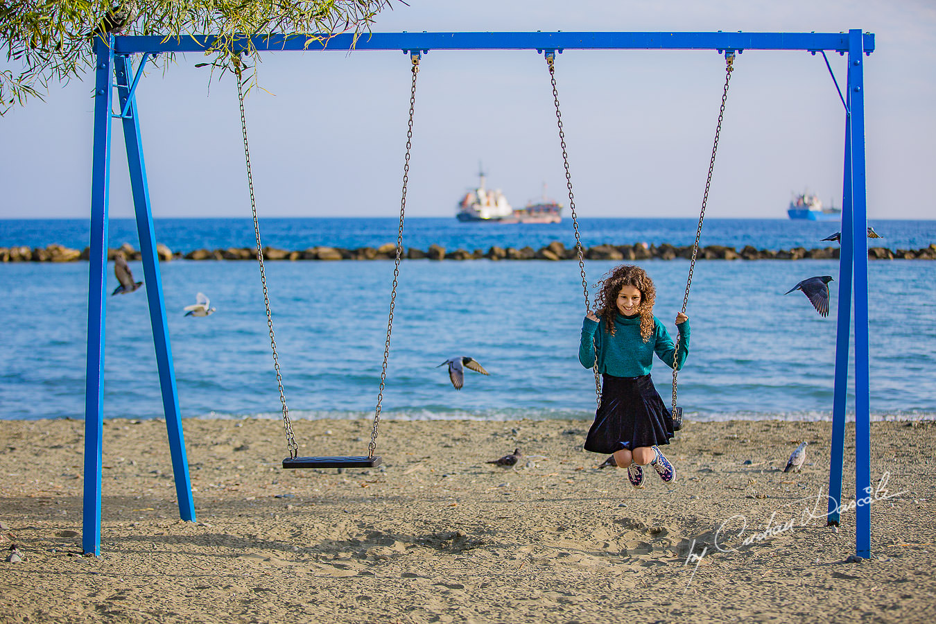 Young lady in the swing on a beach, moments captured by Cristian Dascalu during a beautiful Limassol family photography photo session.