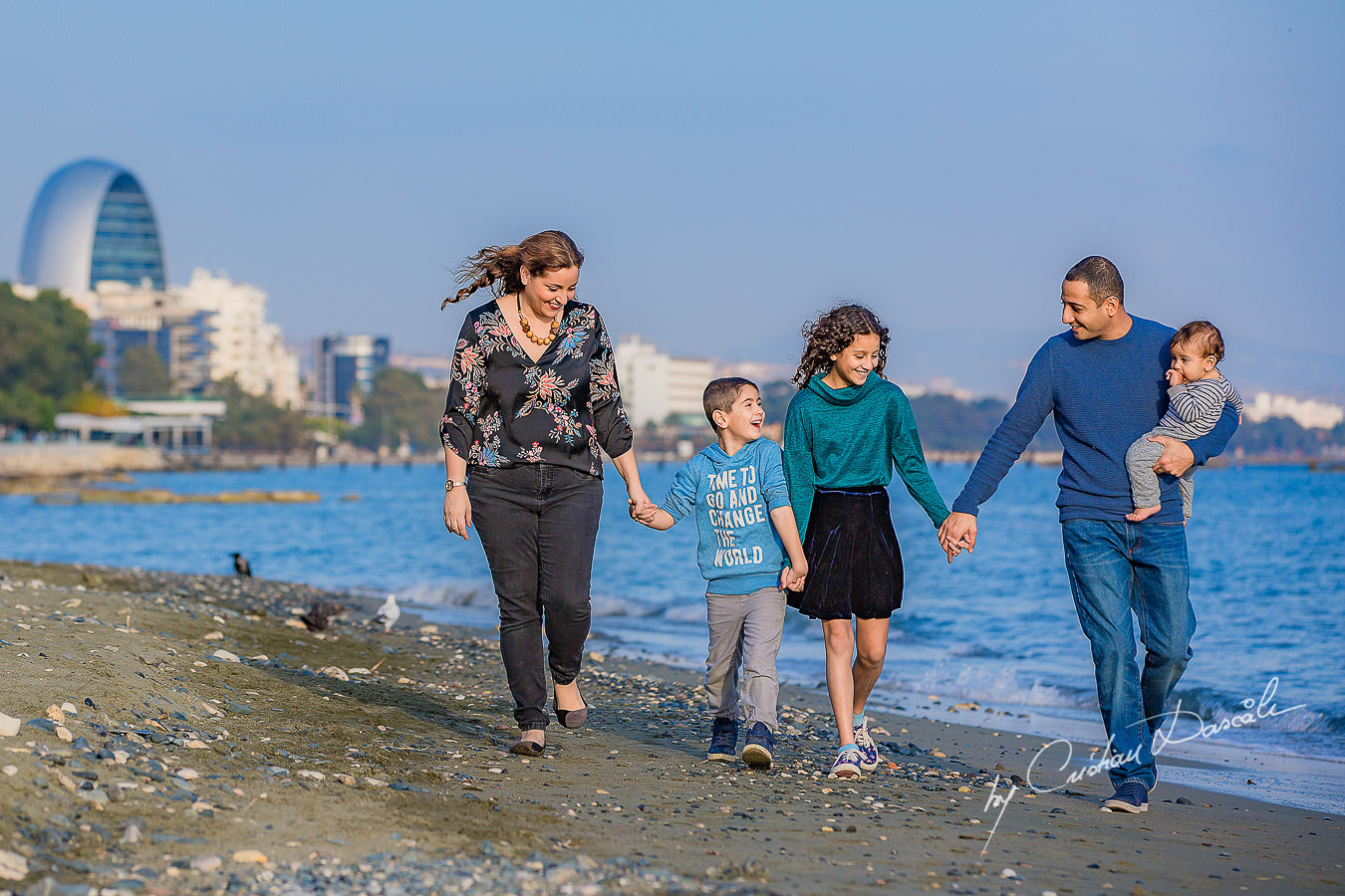 Family walking on a beach, moments captured by Cristian Dascalu during a beautiful Limassol family photography photo session.