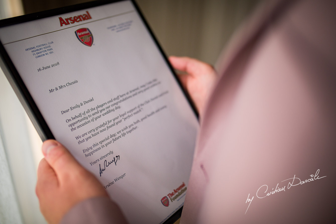 Groom reading the congratulations letter from Arsene Wenger at a Beautiful Wedding at Elias Beach Hotel captured by Cyprus Photographer Cristian Dascalu.
