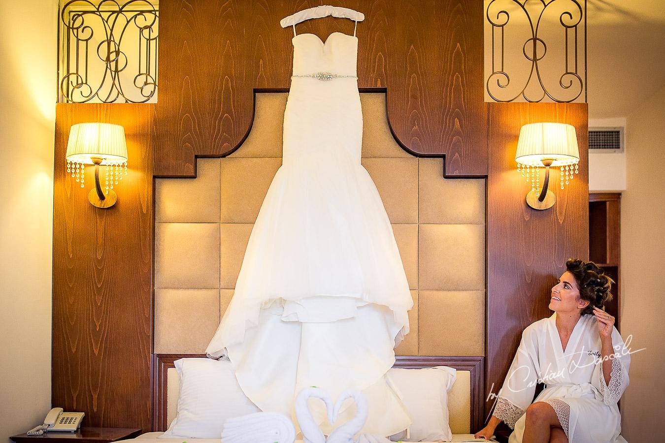 Bride admiring her Wedding Dress at a Beautiful Wedding at Elias Beach Hotel captured by Cyprus Photographer Cristian Dascalu.