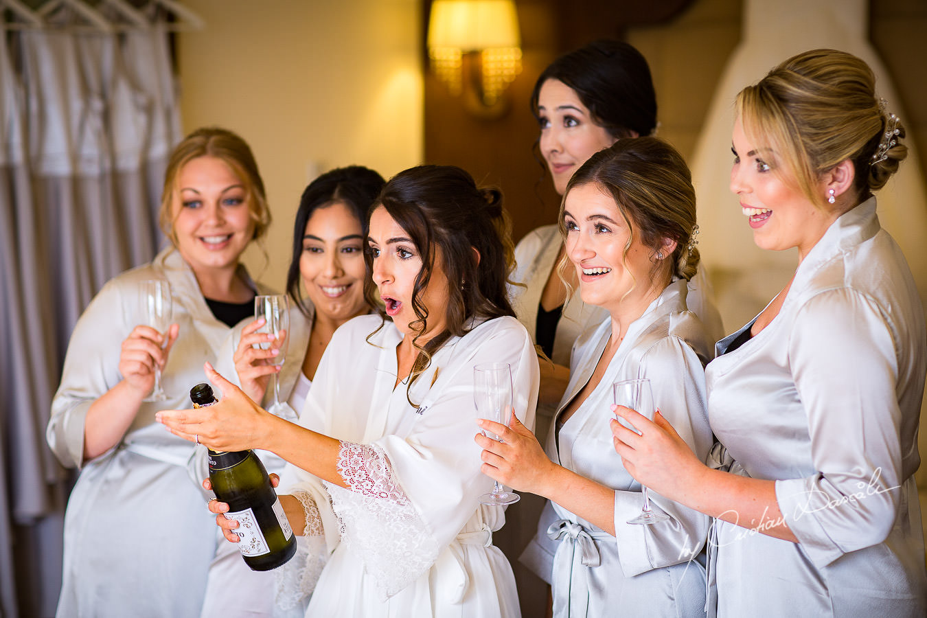 Bride opening champagne during a Beautiful Wedding at Elias Beach Hotel captured by Cyprus Photographer Cristian Dascalu.
