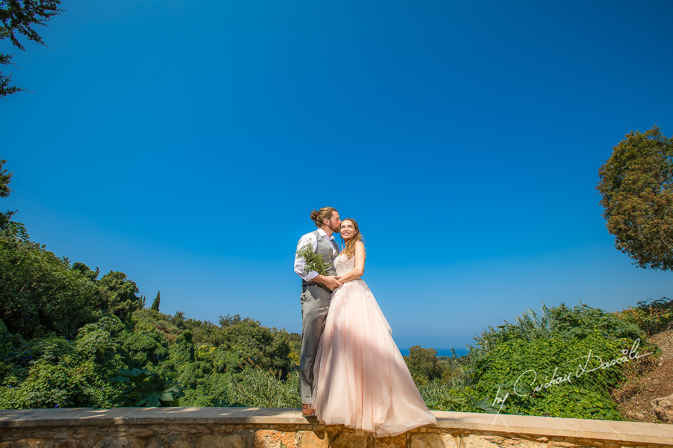 Bride and groom posing on a green garden, moments captured at a Shamanic Wedding Ceremony by Cyprus Wedding Photographer Cristian Dascalu.