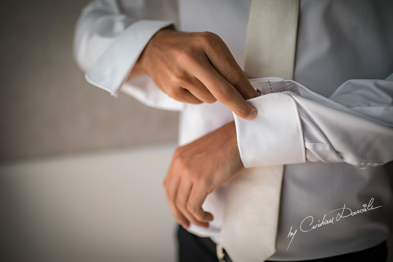 Moments when the groom is wearing his cuff links captured by Cristian Dascalu during an elegant Aphrodite Hills Wedding in Cyprus.
