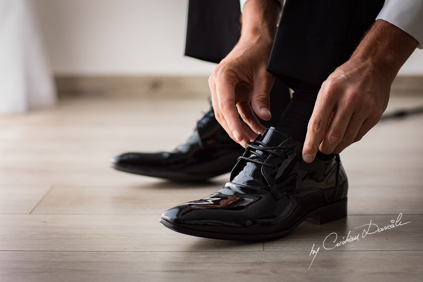 The groom is tying his shoe laces, moments captured by Cristian Dascalu during an elegant Aphrodite Hills Wedding in Cyprus.