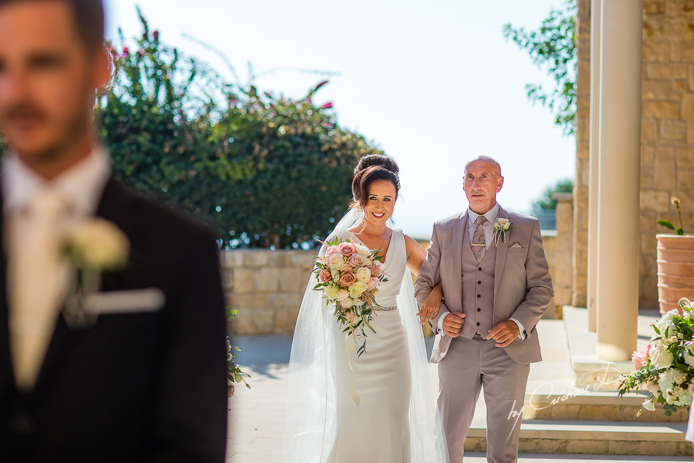 The bride is looking at her handsome groom, moments captured by Cristian Dascalu during an elegant Aphrodite Hills Wedding in Cyprus.
