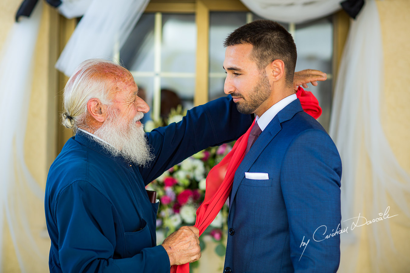 The grandfather of the groom, also the priest`s village is blessing him with the red scarf, moments captured by Cyprus Wedding Photographer Cristian Dascalu at a beautiful wedding in Larnaka, Cyprus.