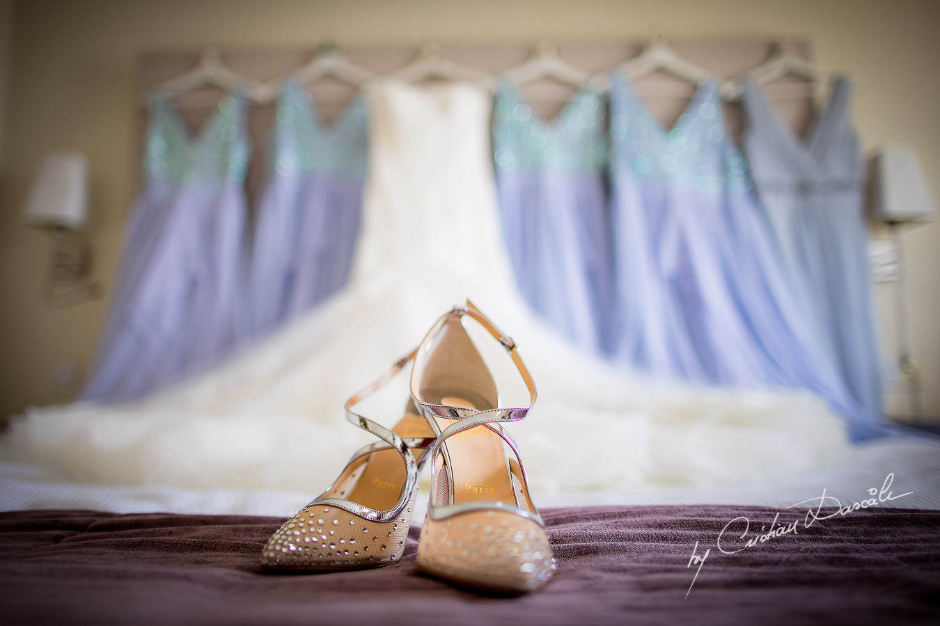 Bridal shoes with the dresses in the background, captured during an Elegant Minthis Hills Wedding, in Paphos, Cyprus.